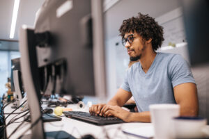Young black programmer meeting regulation software upgrade compliance by upgrading software on a PC in the office.